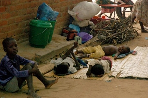 Children resting in the shade to escape the heat in Bangula camp.